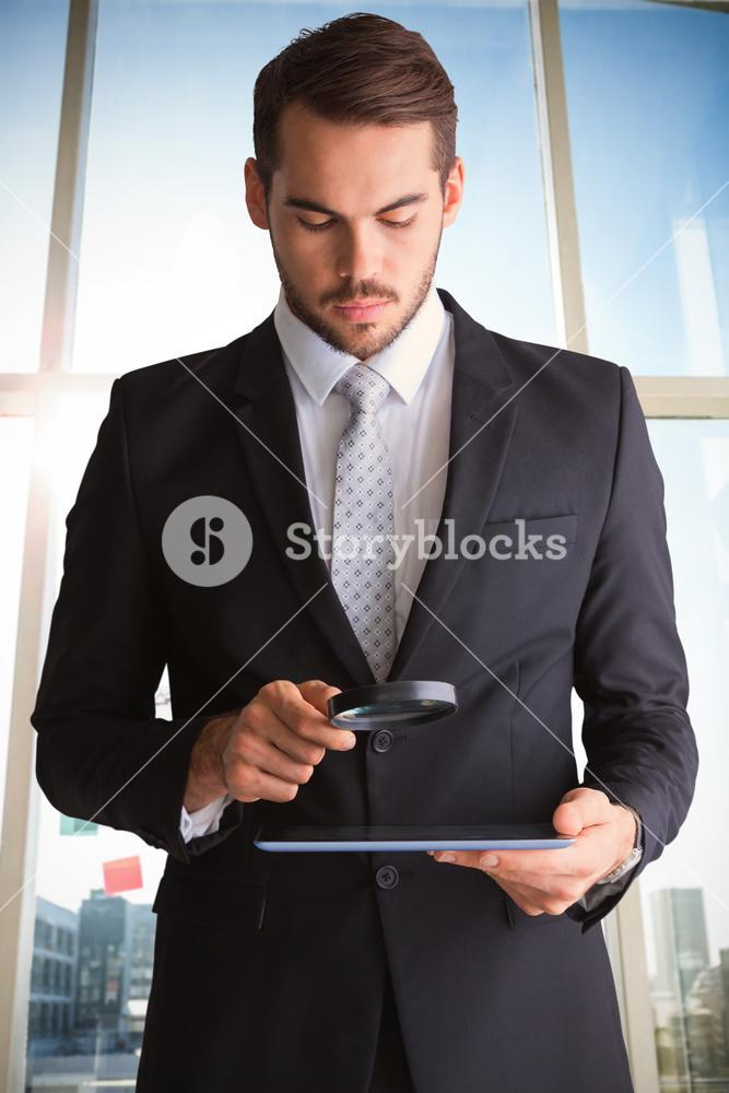 Composite image of concentrated businessman using magnifying glass