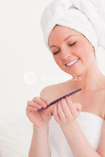 Good looking young woman wearing a towel using a nail file