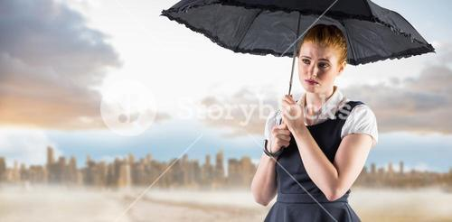 Composite image of pretty redhead businesswoman holding umbrella
