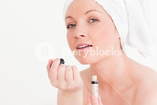Attractive young woman wearing a towel using a lip gloss