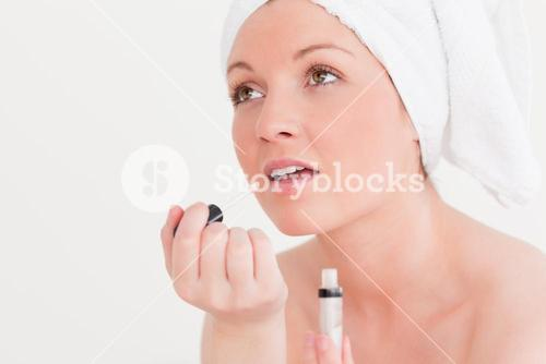 Pretty young woman wearing a towel using a lip gloss