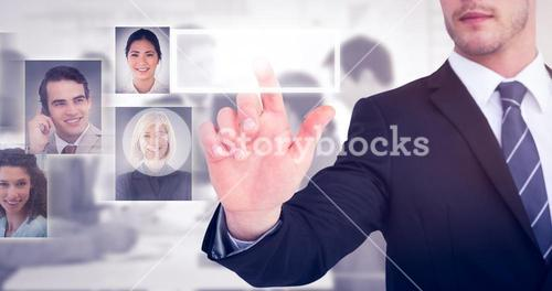 Composite image of focused businessman pointing with his finger