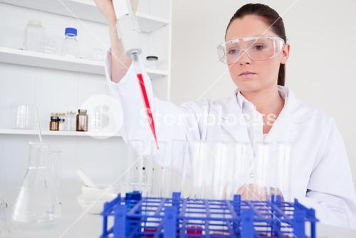 Attractive female biologist holding a manual pipette with sample from test tubes