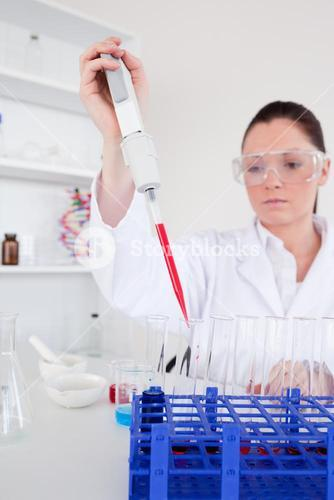 Good looking female biologist holding a manual pipette with sample from test tubes