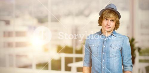 Composite image of serious blond hipster staring at camera