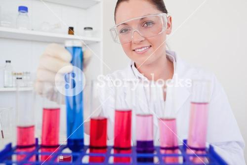 Beautiful redhaired female holding a test tube