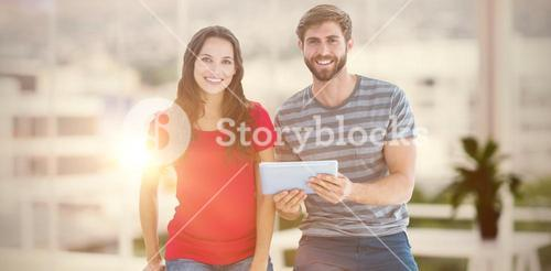 Composite image of couple posing with tablet