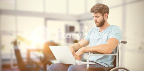 Composite image of man in wheelchair using computer