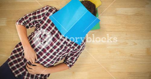 Composite image of creative businessman lying on hardwood floor