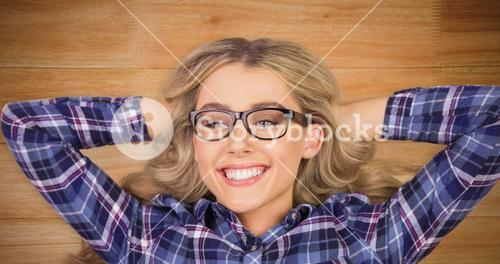 Composite image of a blonde hipster lying on the floor