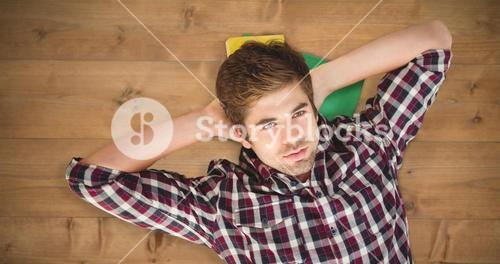 Composite image of hipster with hands behind head lying on hardwood floor