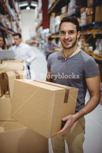 Smiling man carrying box