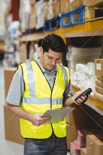 Warehouse worker looking at clipboard