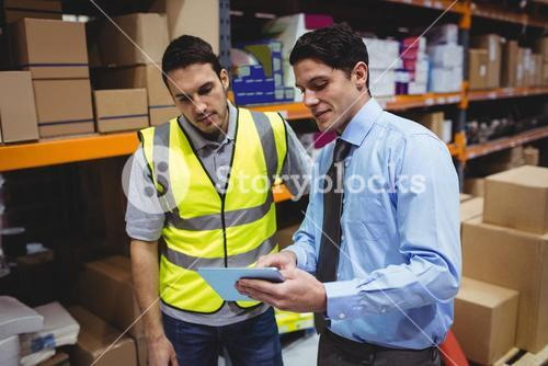 Manager showing tablet to worker