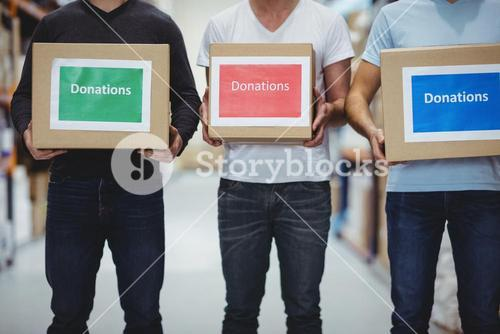 Volunteers smiling at camera holding donations boxes