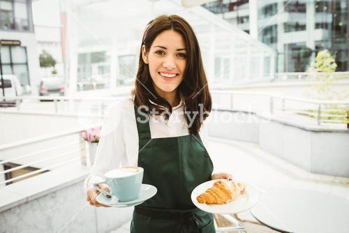 Waitress posing with coffee and croissant
