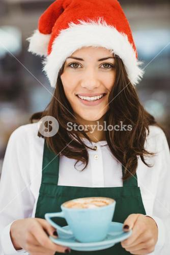 Woman with santa hat holding coffee