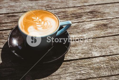 Cup of cappuccino with coffee art on wooden table