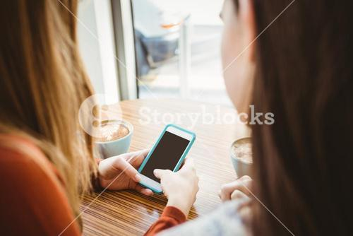 Friends using smartphone and having coffee