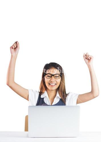 Happy businesswoman using laptop and raising arms