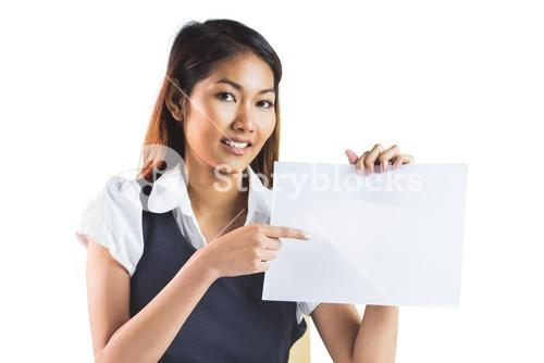 Smiling businesswoman pointing a sheet of paper