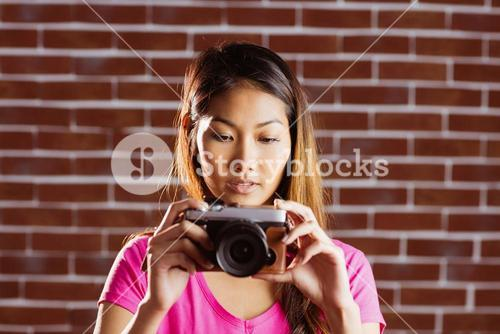 Smiling asian woman taking picture with camera