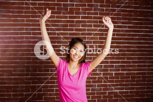 Smiling asian woman raising arms