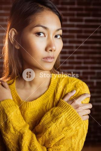 Serious asian woman with hands on shoulders