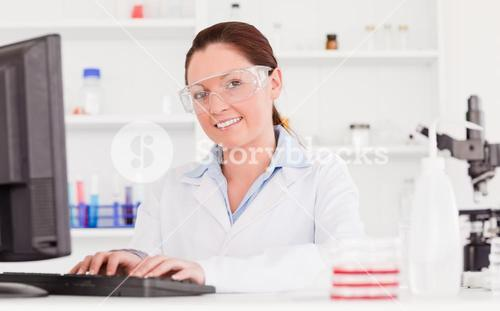 Young scientist typing a report with her computer