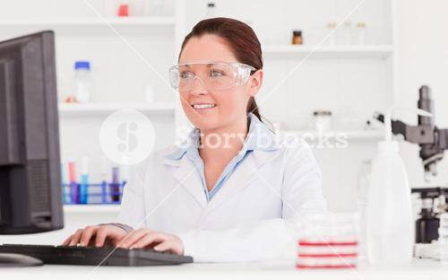Cute scientist typing a report with her computer