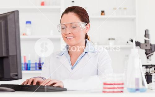 Beautiful scientist typing a report with her computer