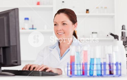 Redhaired scientist typing a report with her computer