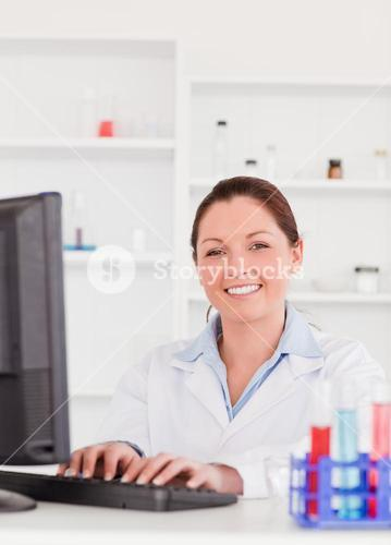 Smiling scientist typing a report with her computer