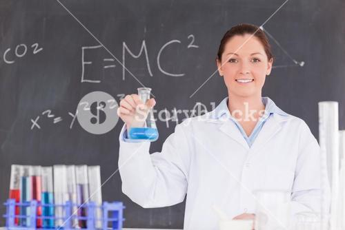 Cute scientist holding a container filled up with a blue liquid