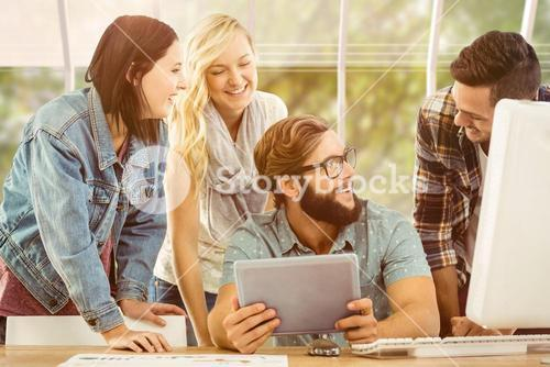 Composite image of happy business people using digital tablet at computer desk