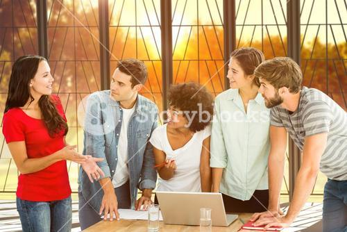 Composite image of colleagues gathered around a laptop at office