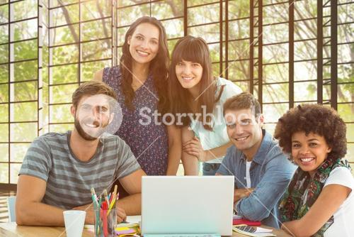 Composite image of happy creative business team gathered around a laptop