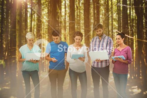 Composite image of group of young colleagues using laptop and tablet