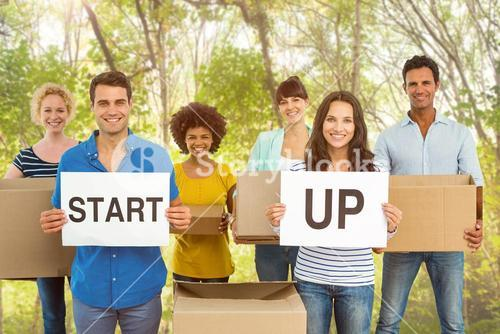 Composite image of creative business team holding cardboard written start up