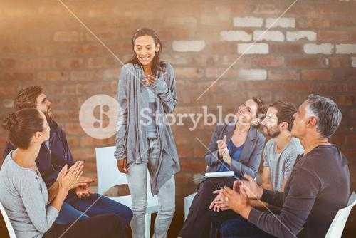 Composite image of  rehab group applauding delighted woman standing up