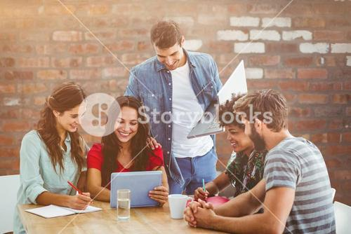 Composite image of creative business team gathered around a tablet