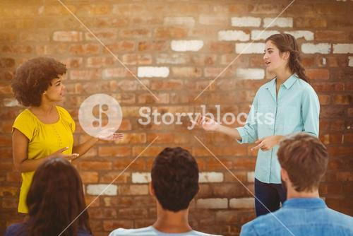 Composite image of casual young businesswoman giving presentation to colleagues