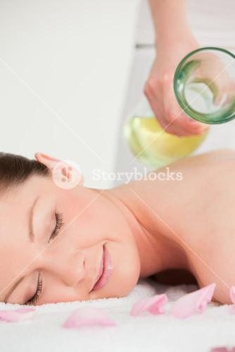 Portrait of a young female having massage oil versed