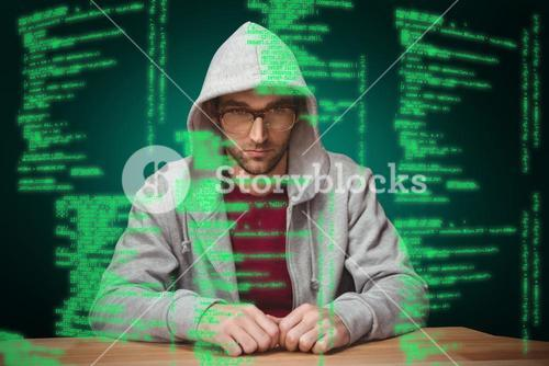 Composite image of thoughtful man with hooded shirt sitting at desk
