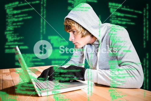 Composite image of focused man with hoodie typing on laptop