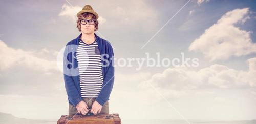 Composite image of serious hipster holding a suitcase