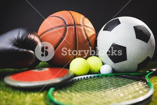 Close up of boxing gloves and basketball football tennis golf balls and discus