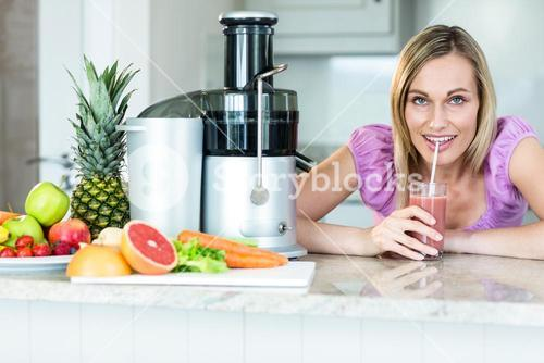 Blonde woman drinking a smoothie in the kitchen