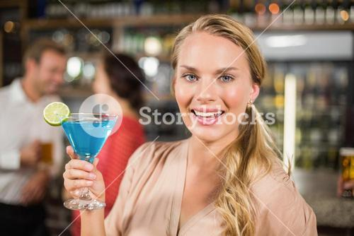 Attractive woman holding cocktail glass facing camera