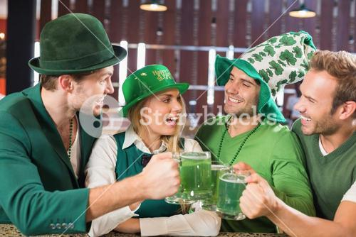 Friends wearing St. Patricks day associated clothes toasting